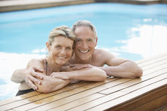 放松在游泳池边缘的夫妇 免版税库存照片
