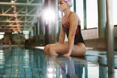 放松在游泳池边缘的运动的适合妇女 库存照片