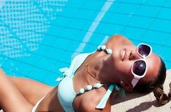 放松在游泳池附近的美丽的少妇 免版税库存图片