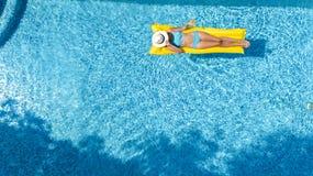 放松在游泳池,在可膨胀的床垫的游泳的美丽的女孩和获得乐趣在水中家庭度假,鸟瞰图 免版税库存图片