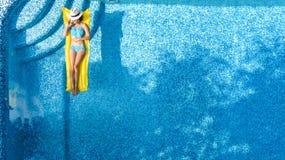 放松在游泳池,在可膨胀的床垫的游泳的美丽的女孩和获得乐趣在水中家庭度假 库存图片