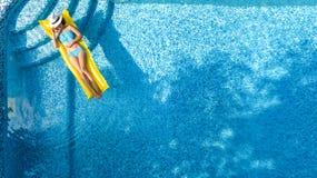 放松在游泳池,在可膨胀的床垫的游泳的美丽的女孩和获得乐趣在水中家庭度假 免版税库存图片