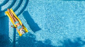 放松在游泳池,在可膨胀的床垫的游泳的美丽的女孩和获得乐趣在水中家庭度假 免版税库存照片