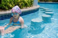 放松在游泳的小逗人喜爱的愉快的女孩 免版税库存照片