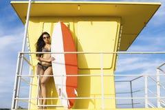 放松在游泳以后的比基尼泳装的年轻冲浪者女性在海洋在夏天 免版税库存照片