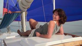 放松在游艇的俏丽的女孩,调情地微笑对照相机 影视素材