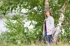 放松在湖岸的典雅的外套的美丽的夫人 免版税图库摄影