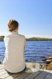 放松在湖岸的妇女 免版税库存图片