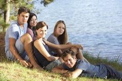 放松在湖岸的小组青年人  免版税图库摄影