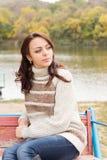 放松在湖的边的可爱的妇女 免版税库存图片
