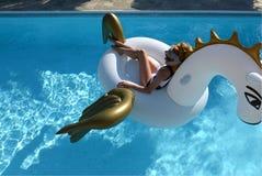 放松在漂浮佩格瑟斯浮游物的大可膨胀的独角兽的豪华游泳池度假旅馆里的妇女 免版税图库摄影
