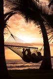 放松在热带吊床的夫妇 库存图片
