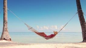 放松在热带海岛海滩的一个吊床的女孩 ?? 股票录像