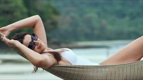 放松在热带海滩的吊床的太阳镜的年轻美丽的妇女 影视素材