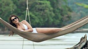 放松在热带海滩的吊床的太阳镜的年轻美丽的妇女 股票视频