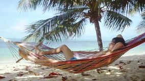 放松在热带海滩的吊床的年轻人 在棕榈树旁边供以人员睡觉在吊床 慢的行动 1920x1080 股票录像