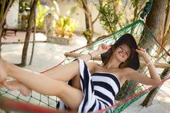 放松在热带海滩在阴影,热的晴天的吊床的妇女 女孩看对与微笑的照相机 图库摄影