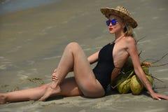 放松在热带海滩的一个黑泳装和帽子的妇女 库存照片