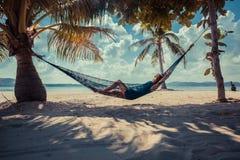 放松在热带海滩的吊床的妇女 图库摄影