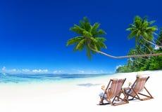 放松在热带海滩的夫妇 库存照片
