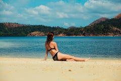 放松在热带海滩的美丽的少妇 免版税库存图片