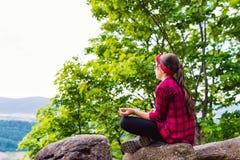 放松在瑜伽姿势的山的健康年轻远足者女孩,愈合 库存图片