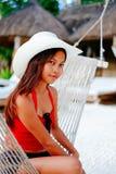 放松在白色沙子海滩的吊床的美丽的少妇在旅行假期时 图库摄影