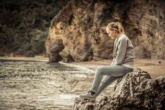 放松在看在减速火箭的葡萄酒s的海滩的一块大峭壁石头的沉思孤独的少妇旅客狂放的山风景 图库摄影