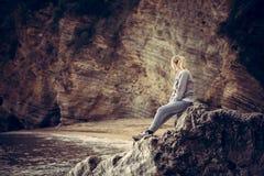 放松在看在减速火箭的葡萄酒s的海滩的一块大峭壁石头的孤独的少妇旅客狂放的山风景 免版税库存照片