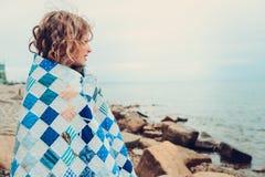 放松在石海滩的逗人喜爱的卷曲愉快的儿童女孩,包裹在舒适被子毯子 库存图片