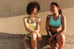 放松在码头的两名微笑的俏丽的体育妇女 库存图片