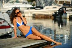 放松在码头的妇女佩带的比基尼泳装和太阳镜 免版税库存照片
