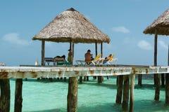 放松在码头的家庭站立在美丽的平静的清楚的海洋水 免版税图库摄影