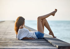放松在码头的性感的美丽的妇女有海视图 免版税库存图片