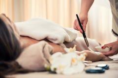 放松在秀丽中心的妇女在皮肤rejuve的治疗期间 免版税库存图片