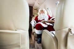 放松在私人喷气式飞机的圣诞老人 免版税库存照片