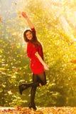 放松在秋天公园投掷的叶子的妇女悬而未决 免版税库存照片