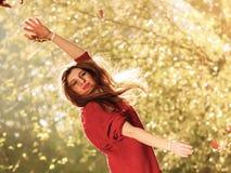放松在秋天公园投掷的叶子的妇女悬而未决 库存图片