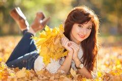 放松在秋天公园的年轻俏丽的妇女 秀丽自然sc 免版税图库摄影