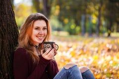 放松在秋天公园的微笑的妇女享用热的饮料咖啡或茶,拿着杯子用温暖的饮料的女性手 免版税库存图片