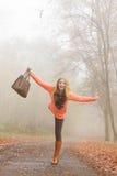 放松在秋天公园的无忧无虑的时尚妇女 免版税库存照片