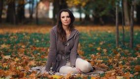 放松在秋天公园的美丽的妇女 免版税库存图片