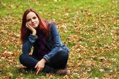 放松在秋天公园的年轻俏丽的妇女 免版税库存图片
