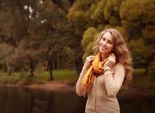 放松在秋天公园的年轻俏丽的妇女 库存图片