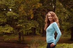 放松在秋天公园的年轻俏丽的妇女 免版税库存照片
