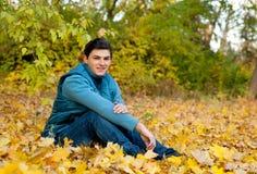 放松在秋天公园的年轻微笑的人 免版税库存图片