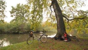放松在秋天公园阅读书,单独开会的美丽的学生女孩在树,自行车下在背景中,晴朗 股票视频
