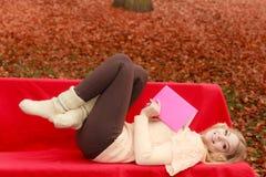 放松在秋天有书的秋天公园的妇女 图库摄影