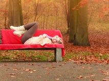 放松在秋天有书的秋天公园的妇女 库存照片