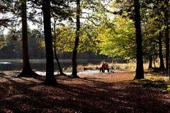 放松在秋天森林里的夫妇 免版税库存图片